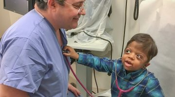 Image of Dr. David Staffenberg with a young patient holding a stethoscope to Dr. Staffenberg's heart.